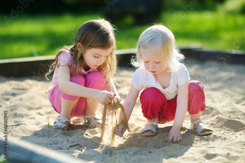 Fotografie, Obraz  Two little sisters playing in a sandbox