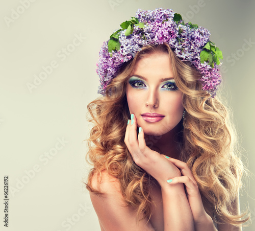 Valokuva  Beautiful model of flowers lilac ,with curly long hair.