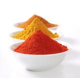 Zmielone przyprawy w miskach - papryka, curry i cynamon