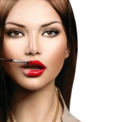 Beauty fashion model girl applying red lipgloss