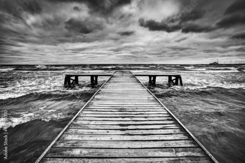 Old wooden jetty during storm on the sea. Dramatic sky