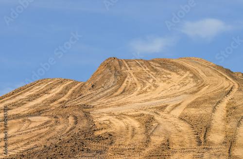 Fotografie, Obraz  Construction dirt pile, tire tracks, blue sky background