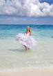 beautiful woman in a dress of the bride runs on waves of the sea