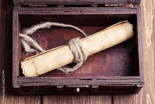 old paper roll inside treasure chest on wooden background Poster