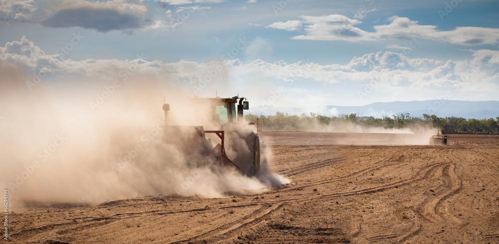 Fototapeta Tractor plowing dry land