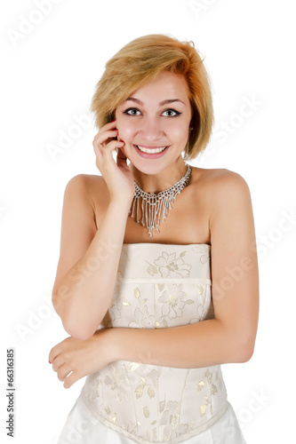 Photo  Happy girl in a white evening dress and necklace. Bare shoulders