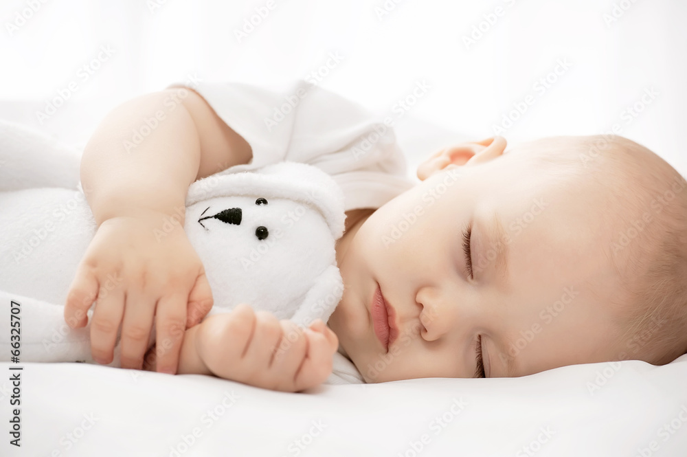 Photo  Carefree sleep little baby with a soft toy on the bed