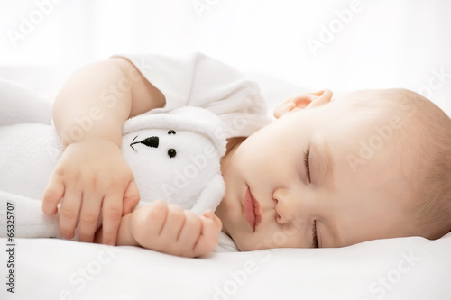 Carefree sleep little baby with a soft toy on the bed Tablou Canvas