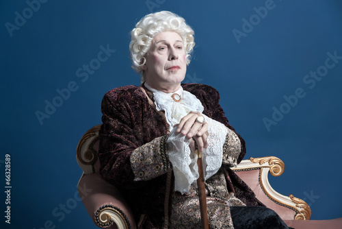 Photo Retro baroque man with white wig holding a walking stick sitting