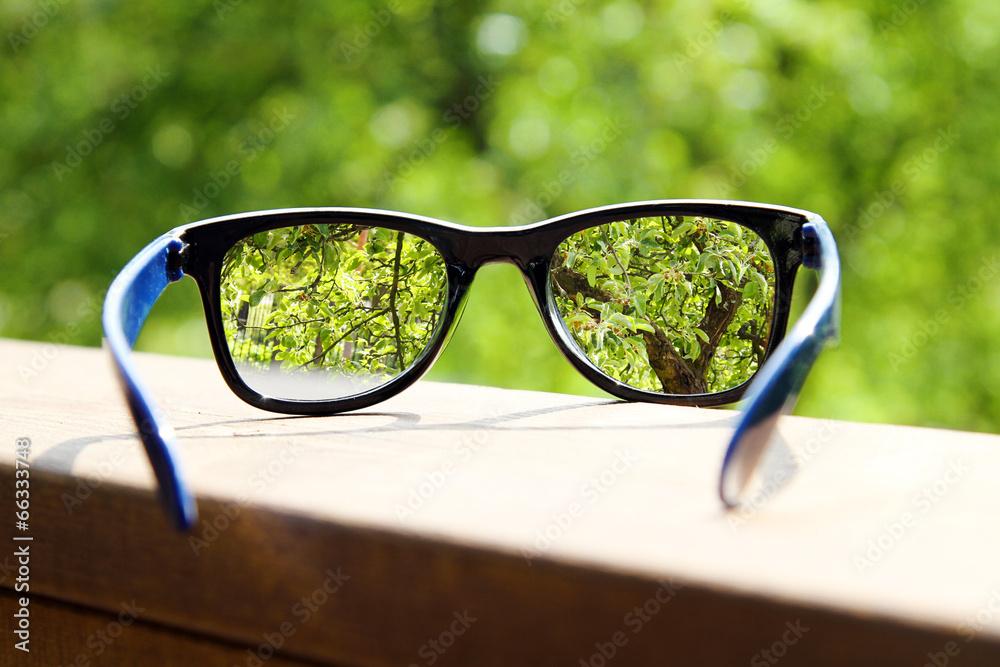 Brille in der Hand über verschwommenes Baum Hintergrund Foto, Poster ...