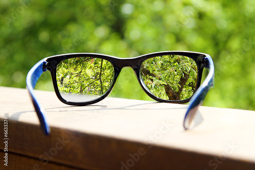 Valokuva  eyeglasses in the hand over blurred tree background