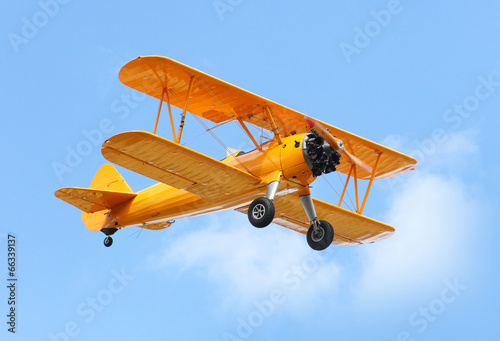 Fotografia, Obraz Yellow biplane on the blue sky.