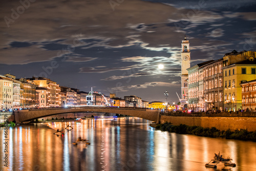 Fotografia Pisa, Italy. City Lungarni illuminated with moonlight during ann