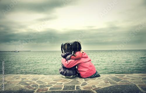 Photo  Two little girls sitting near the sea