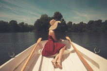 Woman In Rowing Boat Looking A...