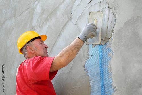Fotografia, Obraz  Wall insulation, mason, worker spreading mortar over mesh