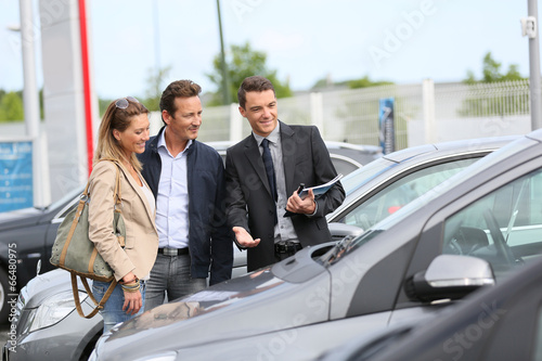 Fotografia, Obraz Car dealer showing vehicles to couple