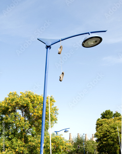 Old shoes hanging from their laces , Buy this stock photo