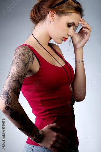 Молодая девушка в красной майке с татуировкой