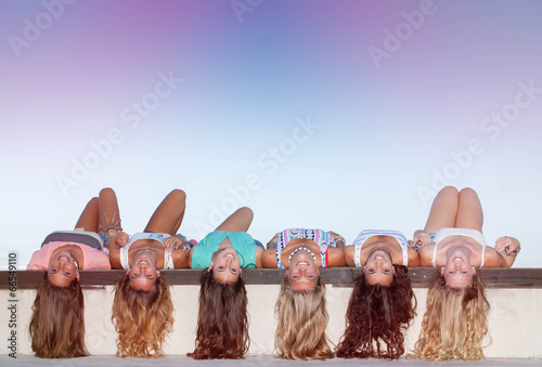 фотография  happy teens with long healthy hair laying upside down.