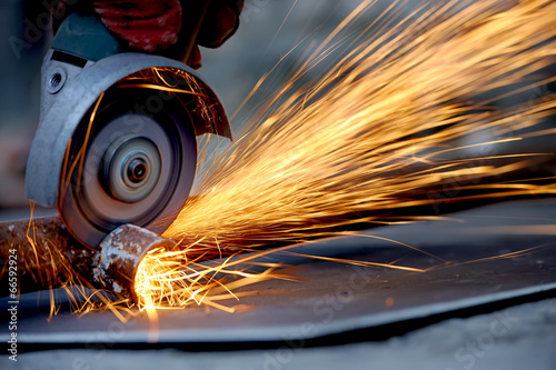 Photo  Worker cutting metal with grinder