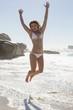 Beautiful smiling woman in white bikini leaping on the beach