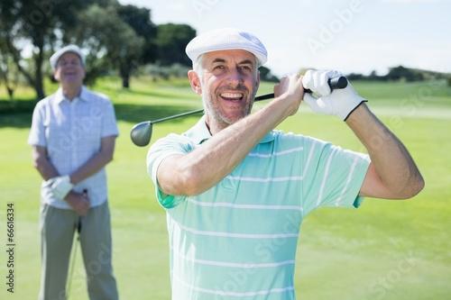 Deurstickers Golf Golfer swinging his club with friend behind him