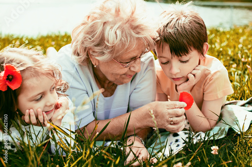 Obraz happy grandmother with grandchildren outdoors - fototapety do salonu