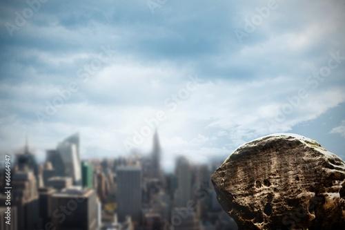 Fototapeta Large rock overlooking urban city obraz na płótnie