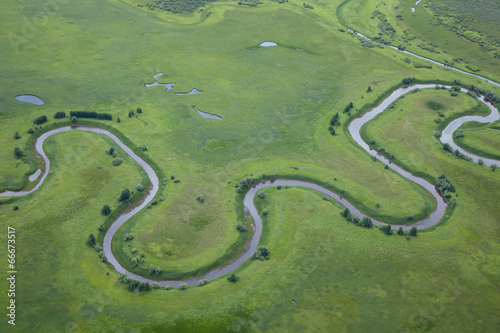 Poster Olive aerial view over the small river on the green grassland