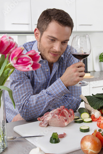 At the end of work: single man drinking glass of wine in the
