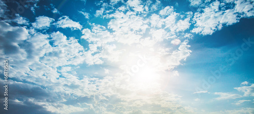 shining sun with lens flare. Blue sky with clouds background