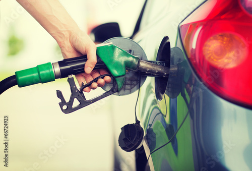 Valokuvatapetti man pumping gasoline fuel in car at gas station