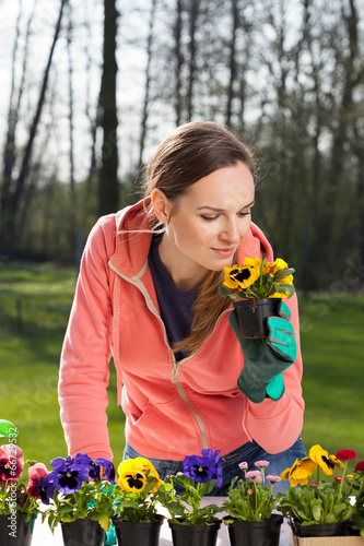Papiers peints Pansies Woman smelling pansy flowers in pot
