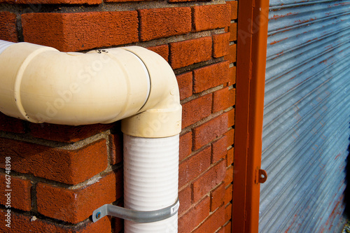 Valokuvatapetti stormwater pipe or downspout hanging on the corner of the house