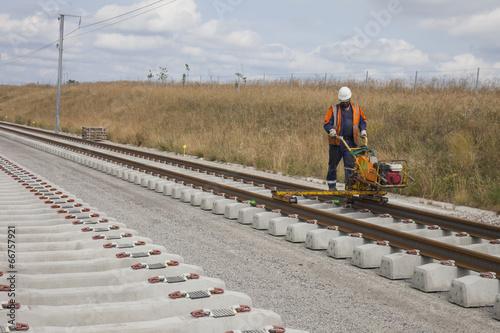 Photo sur Toile Voies ferrées ouvrier fixant des rails
