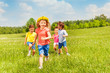 canvas print picture Happy running kids in green field during summer