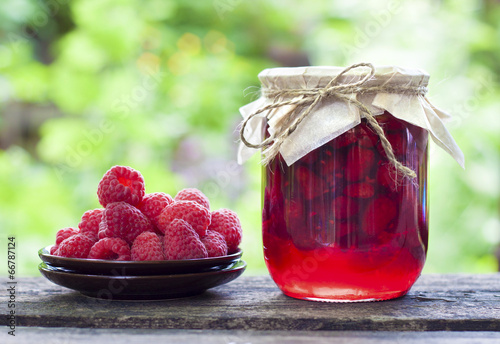 Photo  Raspberry preserve in glass jar and fresh raspberries on a plate