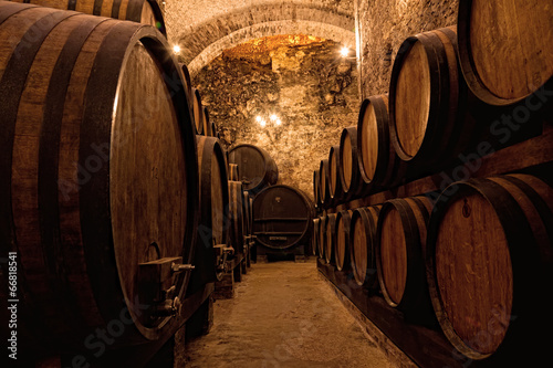 Fotografiet Wooden barrels with wine in a wine vault, Italy