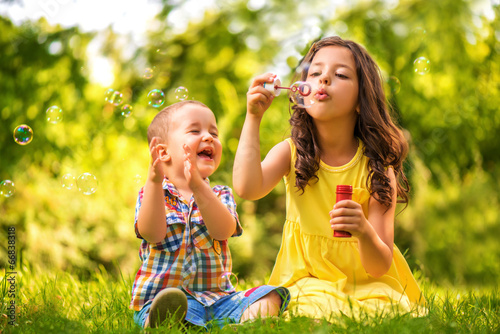 Little girl and boy playing with soap bubbles