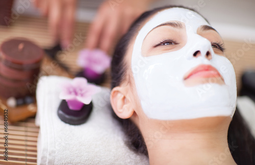 Fotografie, Obraz  Spa therapy for young woman having facial mask at beauty salon