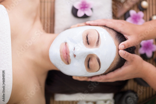 Foto Spa therapy for young woman having facial mask at beauty salon