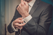 Groom Clasps Cuff Links On A S...