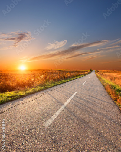 Driving on an empty aspalt road at sunset