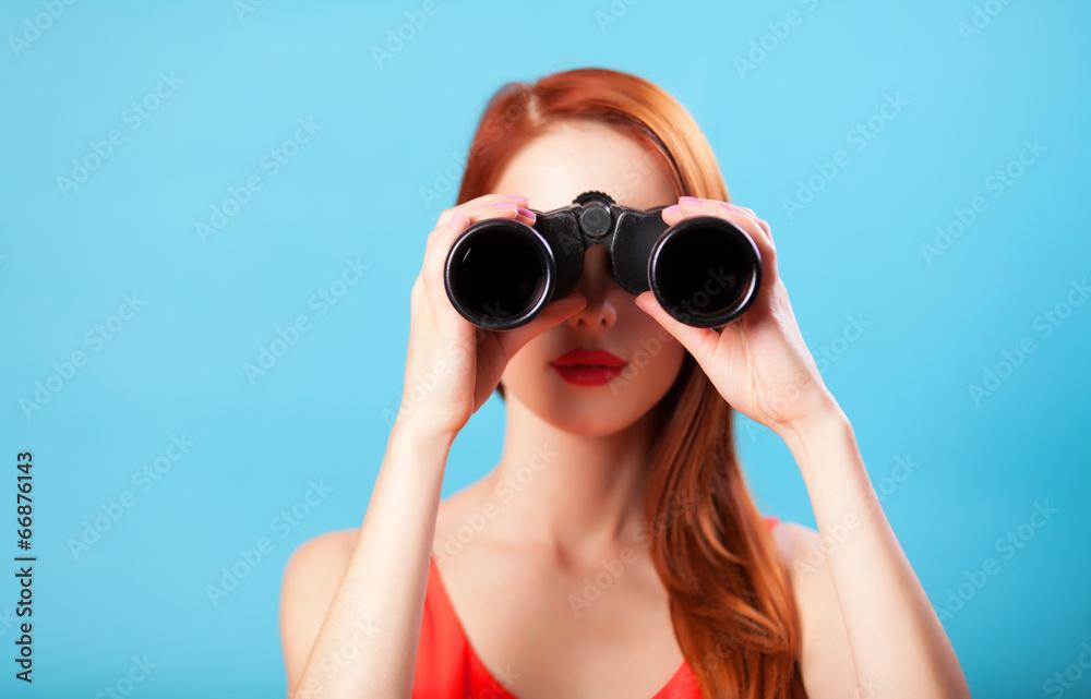 Fototapeta Redhead girl with binocular on blue background.