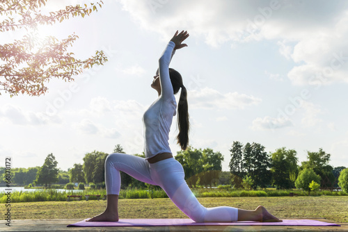 Foto  Pretty woman doing yoga exercises in the park.
