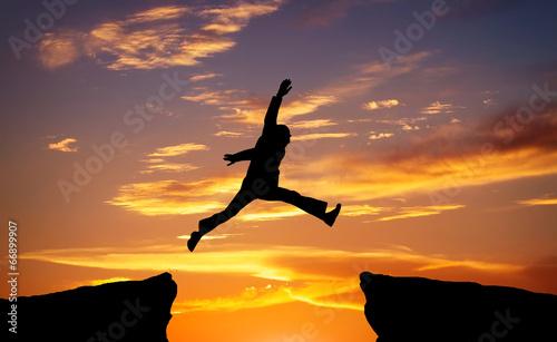 Man jump through the gap on sunset fiery background.