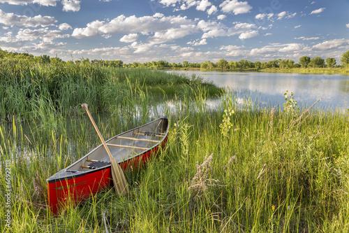 Fotografia  red canoe on lake shore