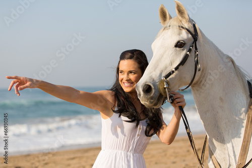 Photo  happy woman pointing at distance with her horse