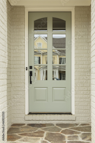 Light Green Front Door To White Brick Home Buy This Stock Photo